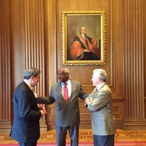 Supreme Court Justice Clarence Thomas (center) talks with Canisius professors Bob Klump, Esq. (left) and Dr. Peter Gaile (right)